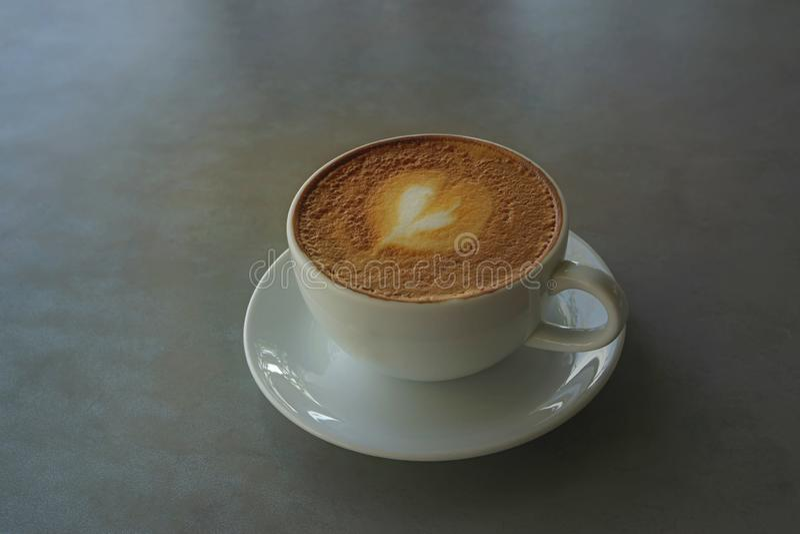 Smakowity pi?, fili?anka dekoruj?ca z serce wzorem na br?zu mleku capuccino kawa spienia w bia?ej ceramicznej fili?ance na szaro? zdjęcie royalty free