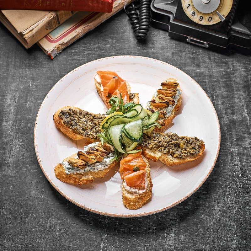 Smakowity różnorodny włoch ściska z owoce morza przeciw nieociosanemu drewnianemu tłu Crostini z serem, czerwieni ryba, cytryna fotografia royalty free