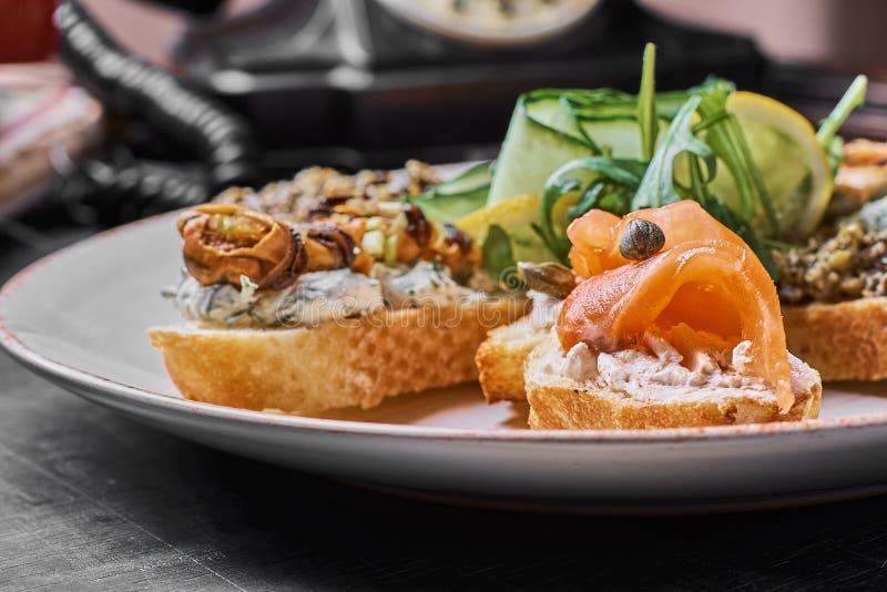 Smakowity różnorodny włoch ściska z owoce morza przeciw nieociosanemu drewnianemu tłu Crostini z serem, czerwieni ryba, cytryna obrazy stock
