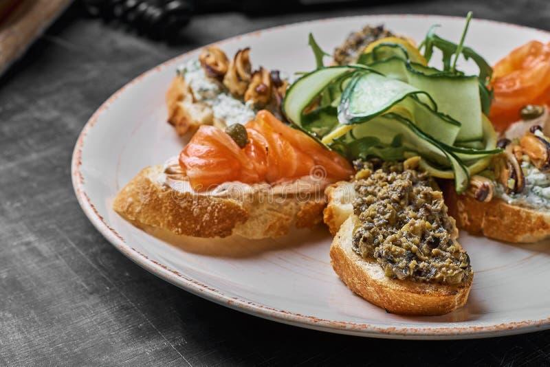 Smakowity różnorodny włoch ściska z owoce morza przeciw nieociosanemu drewnianemu tłu Crostini z serem, czerwieni ryba, cytryna zdjęcie royalty free