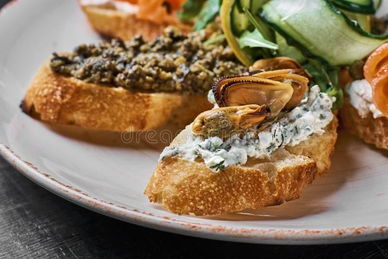 Smakowity różnorodny włoch ściska z owoce morza przeciw nieociosanemu drewnianemu tłu Crostini z serem, czerwieni ryba, cytryna zdjęcie stock