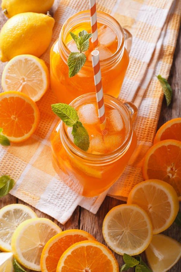 Smakowity sok pomarańczowy z cytryny, lodu i mennicy zakończeniem na tabl, obraz stock