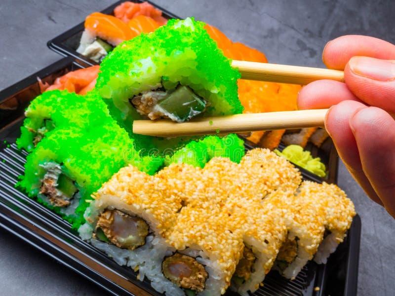 Smakowity suszi bar, Je suszi z chopsticks Kalifornia suszi rolka ustawia z łososiem, warzywa, ryba, kawioru zbliżenie Japonia fotografia stock