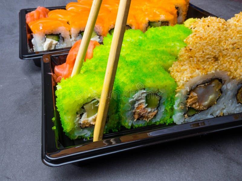 Smakowity suszi bar, Je suszi z chopsticks Kalifornia suszi rolka ustawia z łososiem, warzywa, ryba, kawioru zbliżenie Japonia fotografia royalty free