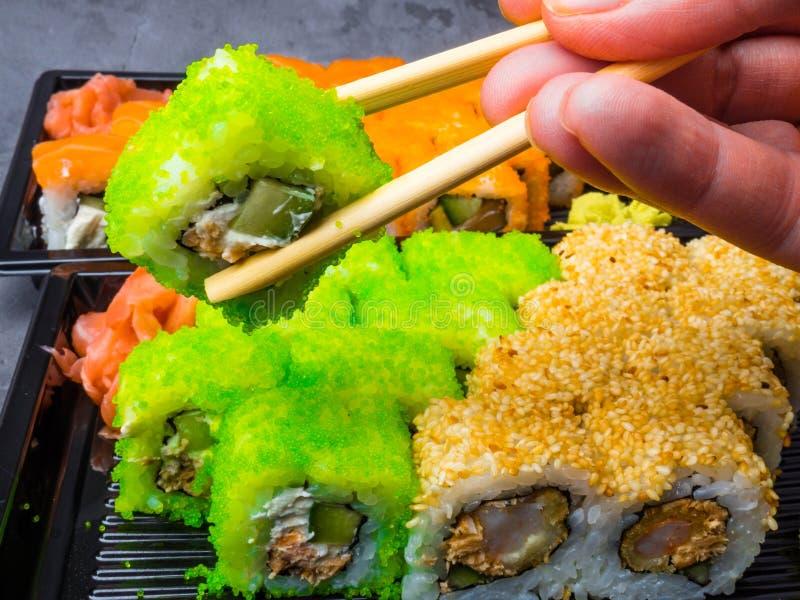 Smakowity suszi bar, Je suszi z chopsticks Kalifornia suszi rolka ustawia z łososiem, warzywa, ryba, kawioru zbliżenie Japonia zdjęcie royalty free