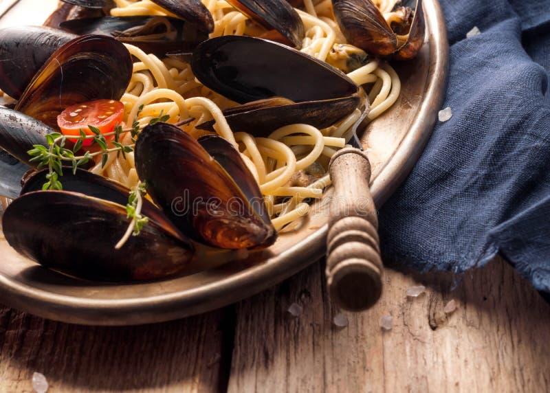 Smakowity Włoski makaron z mussels w czerni łuska w metalu złotym talerzu z rozwidleniem obraz royalty free