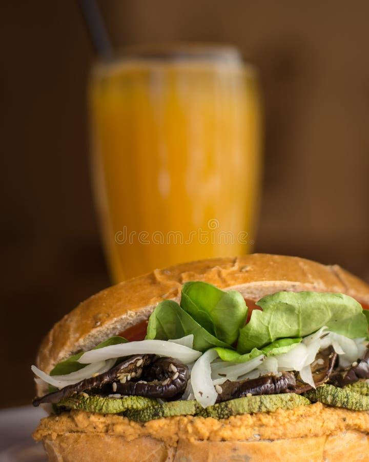 Smakowity weganinu hamburger z sokiem pomarańczowym w tle zdjęcie stock