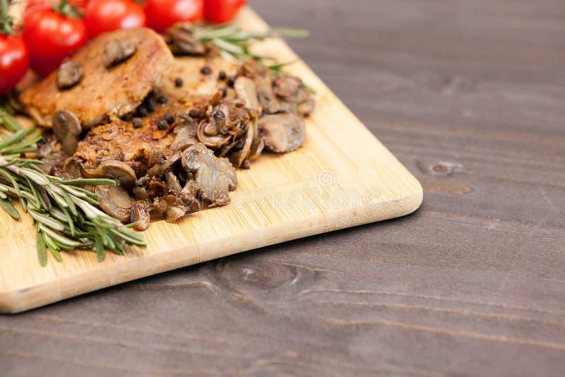 Smakowity wieprzowiny mięso z piec na grillu pieczarkami obok oregano gałąź obraz royalty free