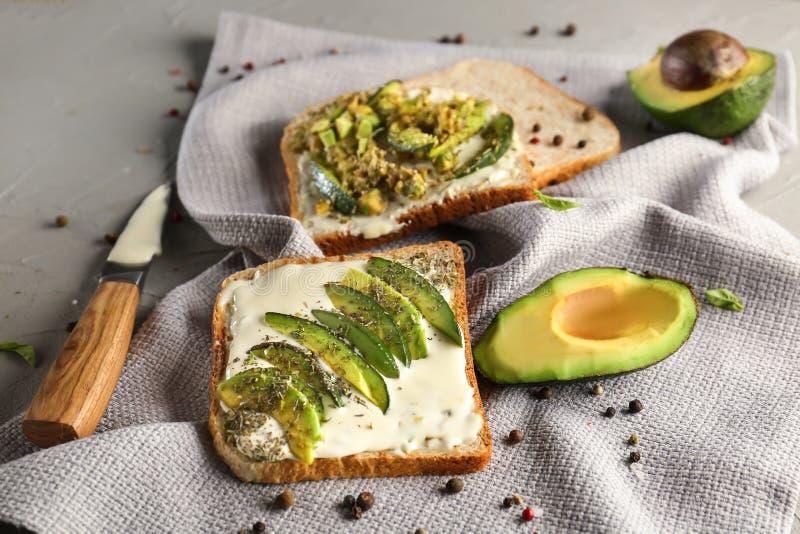 Smakowity wznoszący toast chleb z avocado na popielatym stole zdjęcie stock