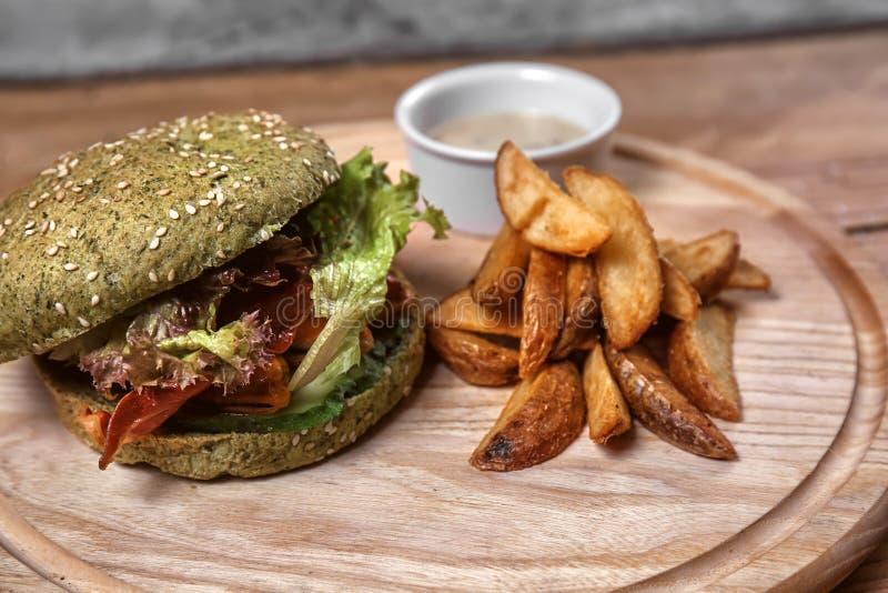 Smakowity zielony hamburger z smażącą grulą na drewnianej desce fotografia stock