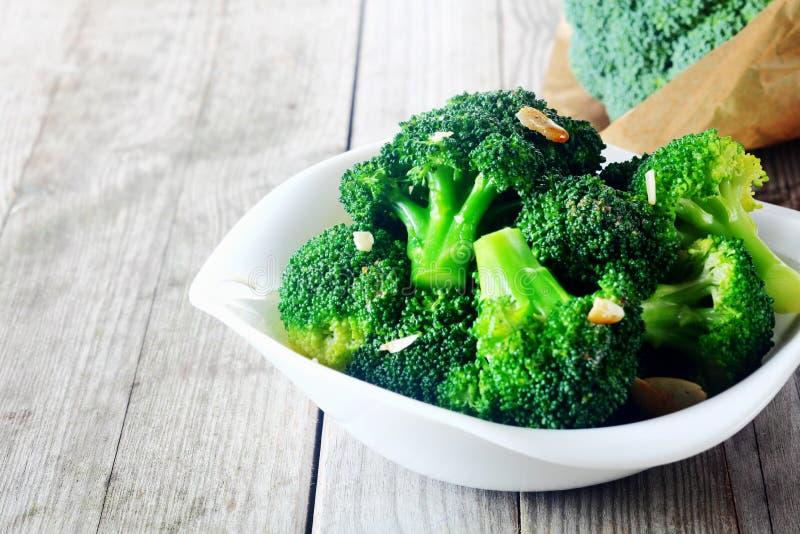 Smaksatt ångad broccoli på den vita plattan royaltyfria bilder