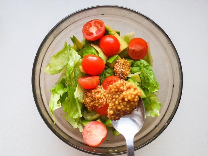 Smaktillsats för grönsaksallad som tillfogar fransk senap till grönsaksallad, Vigatarian mat, sund mat Kvinnligt hälla för kock s royaltyfria bilder