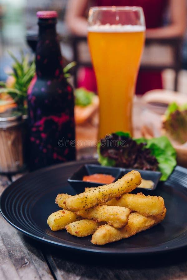 Smaktillsatspommes frites tjänade som med majonnäs och tusen ösås i svart platta med ett exponeringsglas av öl i bakgrunden arkivfoto