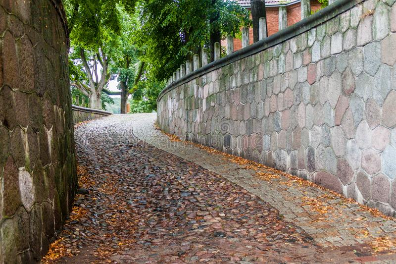 Smal brant lappad gränd i Kaunas, Lithuan arkivbilder