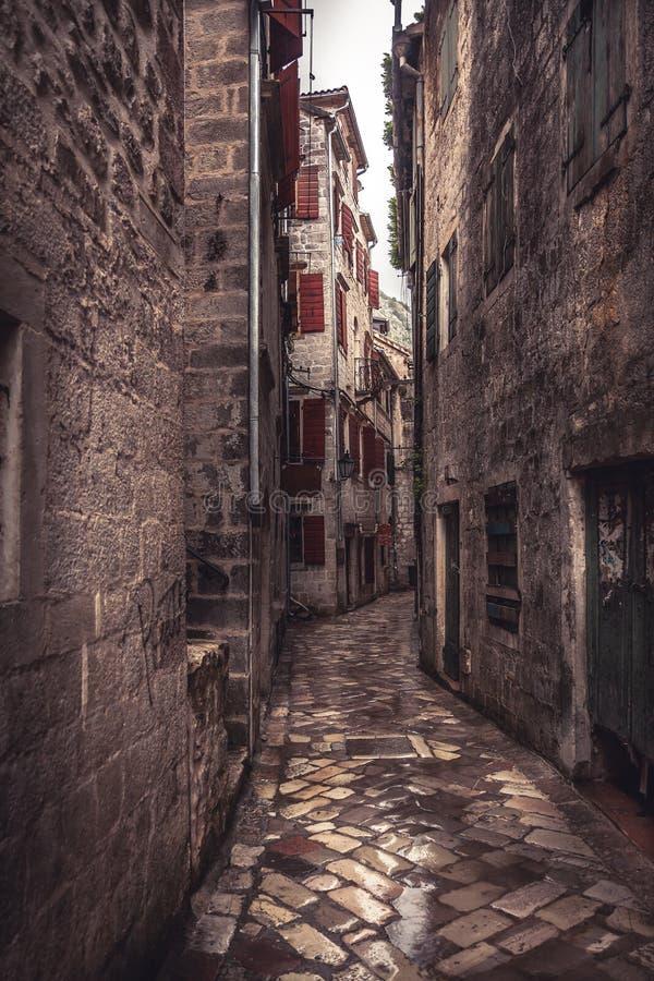 Smal gata för medeltida tappning med forntida stenpavers med medeltida byggnader i den gamla europeiska staden Kotor i Montenegro arkivfoton