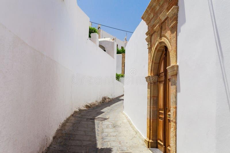Smal gata i den Lindos staden på den Rhodes ön, Dodecanese, Grekland Härliga sceniska gamla forntida vita hus med blommor ber?mdt arkivfoton