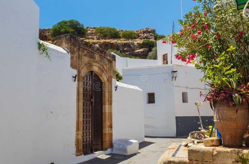 Smal gata i den Lindos staden p? den Rhodes ?n, Dodecanese, Grekland H?rliga sceniska gamla forntida vita hus med blommor ber?mdt arkivbilder