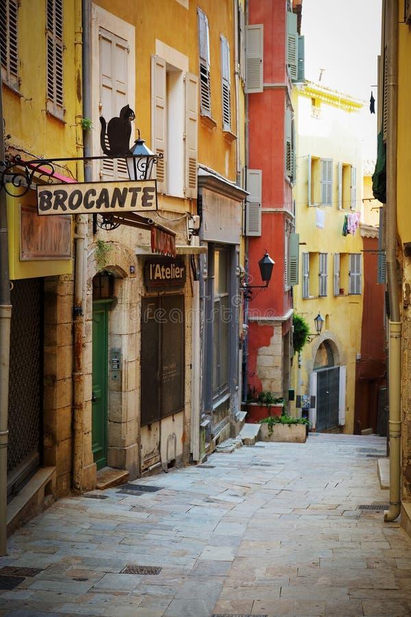 Smal gata med blommor i den gamla staden i Frankrike royaltyfria bilder