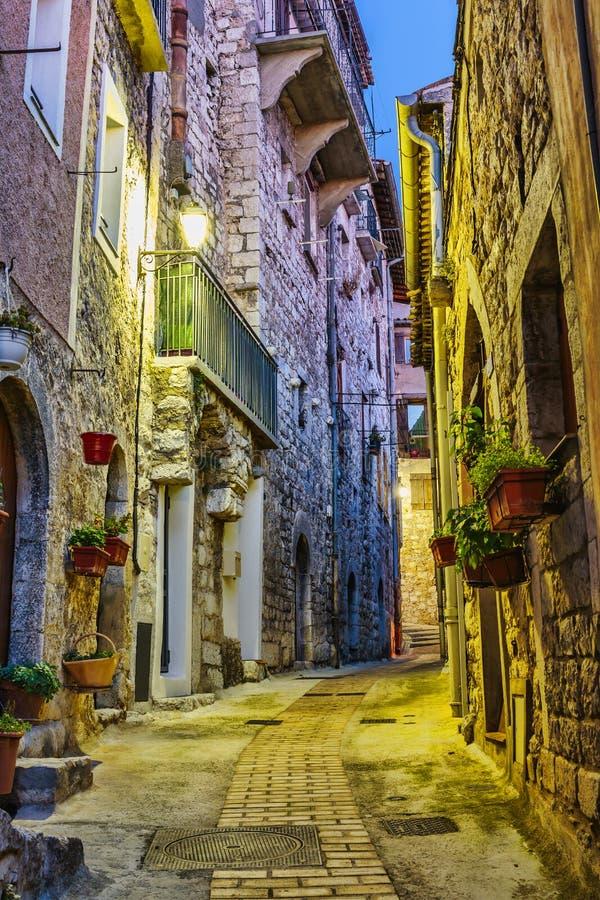 Smal gata med blommor i den gamla staden Peille i Frankrike Nig arkivfoto
