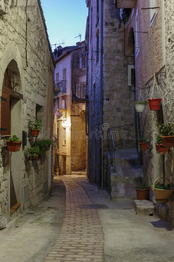 Smal gata med blommor i den gamla staden Peille i Frankrike Nig arkivfoton