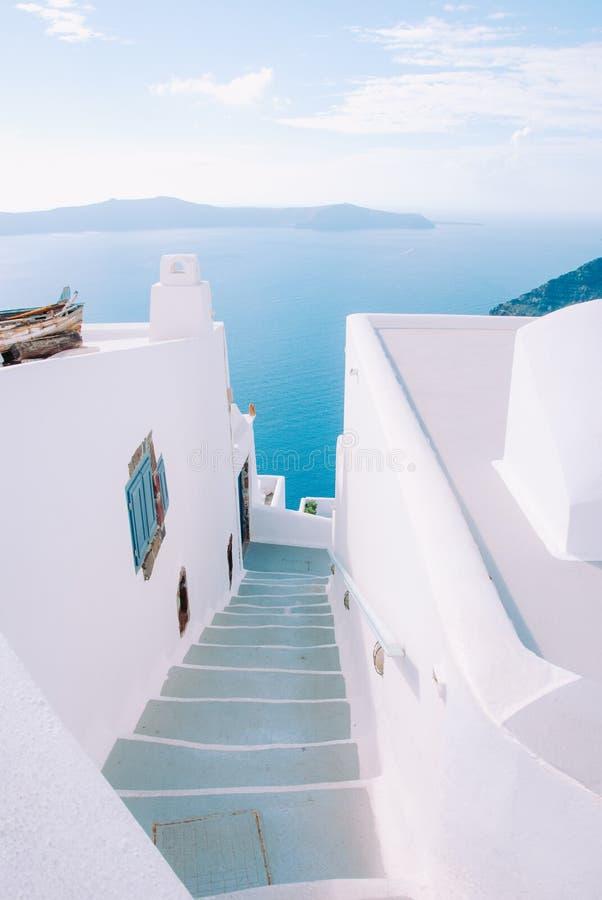 Smal gata på ön av Santorini med moment som ner går till havet arkivfoton