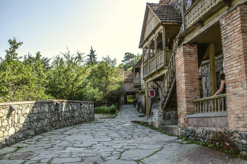 Smal gränd med gamla hus som göras av grova sten- och tegelstenkolonner, med träsned balkonger i museet Tufenkian gamla Dilija arkivfoto