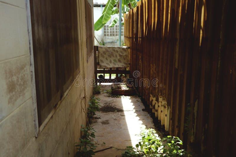 Smal gränd mellan huset och trästaketet - thailändsk trädgård för tappning arkivfoton