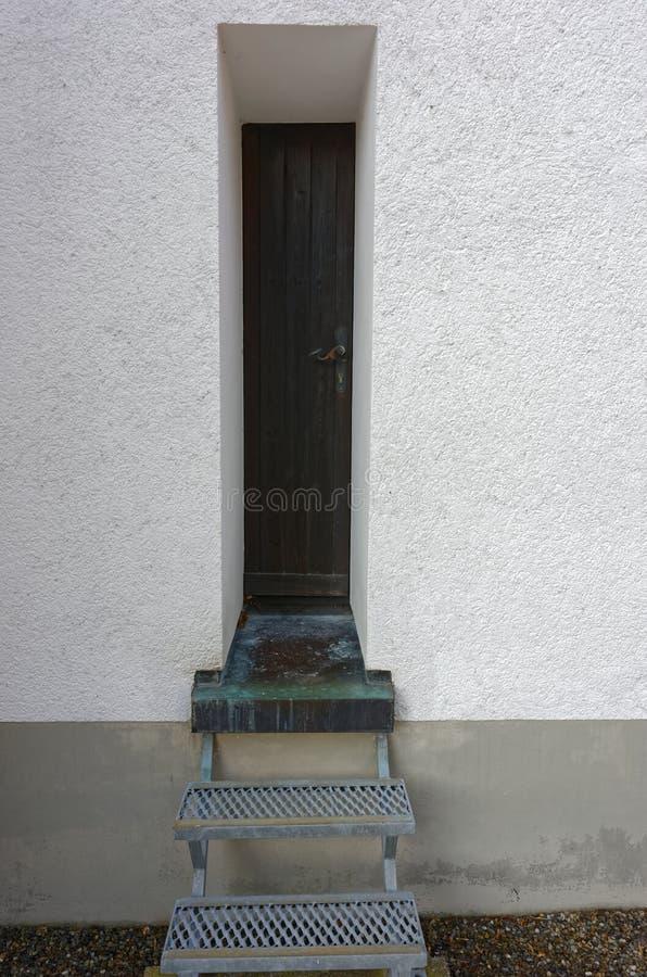 Smal ingångsdörr arkivbild