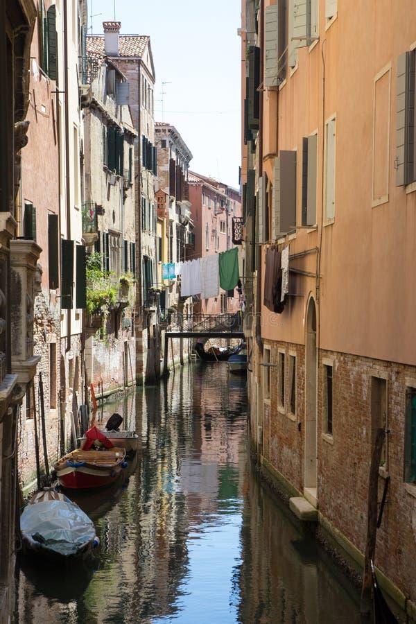Smal kanaal in Venetië met vastgelegde gondels en voorgevels van oude huizen stock foto