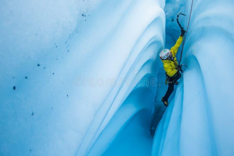 Smal kanjon av is med krabba väggar och en isklättrare som stiger den smala springan royaltyfri bild