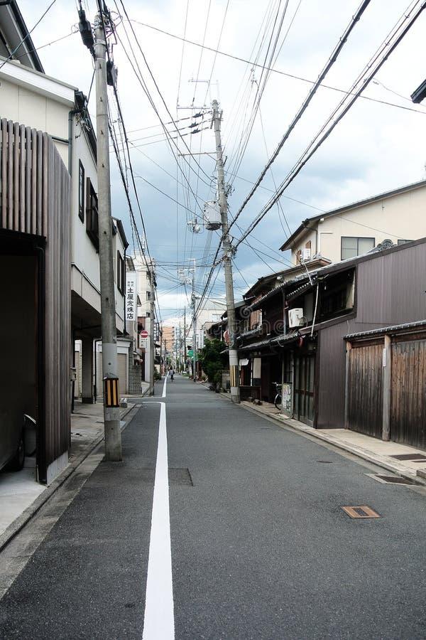 Smal lantlig gata i stad av Kyoto med gamla traditionella japanska byggnader som göras av trä och krokiga maktpoler royaltyfria bilder