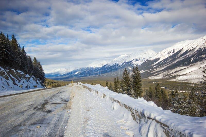 Smal och hal vinterväg med stora snowbanks som buktar ner från berget, Banff nationalpark, Kanada arkivbilder