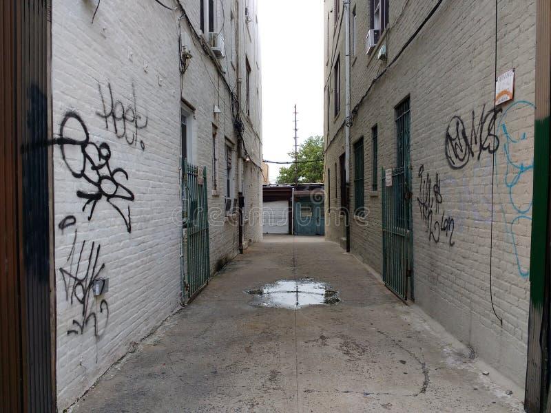 Smal passage mellan byggnader, gränd, Astoria, Queens, NYC, USA arkivfoto