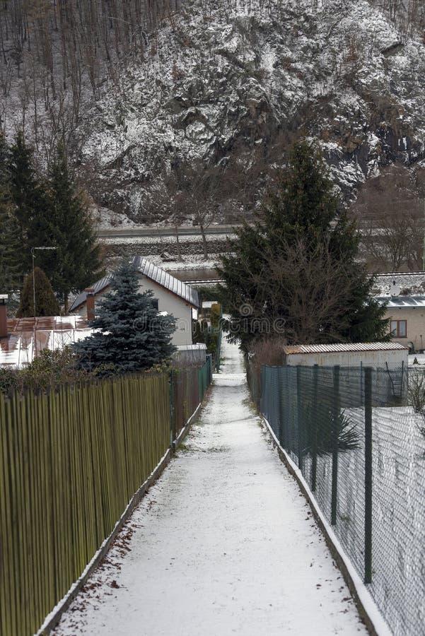 Smal snöig bana mellan sluttande staket och att leda för stugor royaltyfria foton