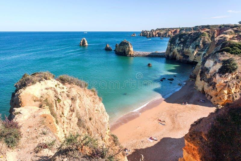 Smal strand in toneelklippen en kust van Portugal Oceaangolven op vreedzaam en zonnig gebied van Algarve stock afbeelding