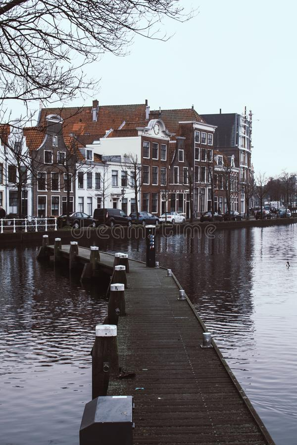 Smal träbro över vattnet av floden Spaarne i Haarlem, Nederländerna Traditionella holländska hus på en bakgrund arkivfoto
