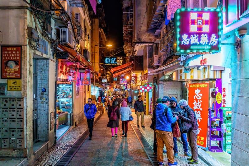 Smal upptagen upplyst portugisisk gata i historisk mitt för Macao stad Folket går i neonannonser och lagrar skyltnattljus royaltyfri bild