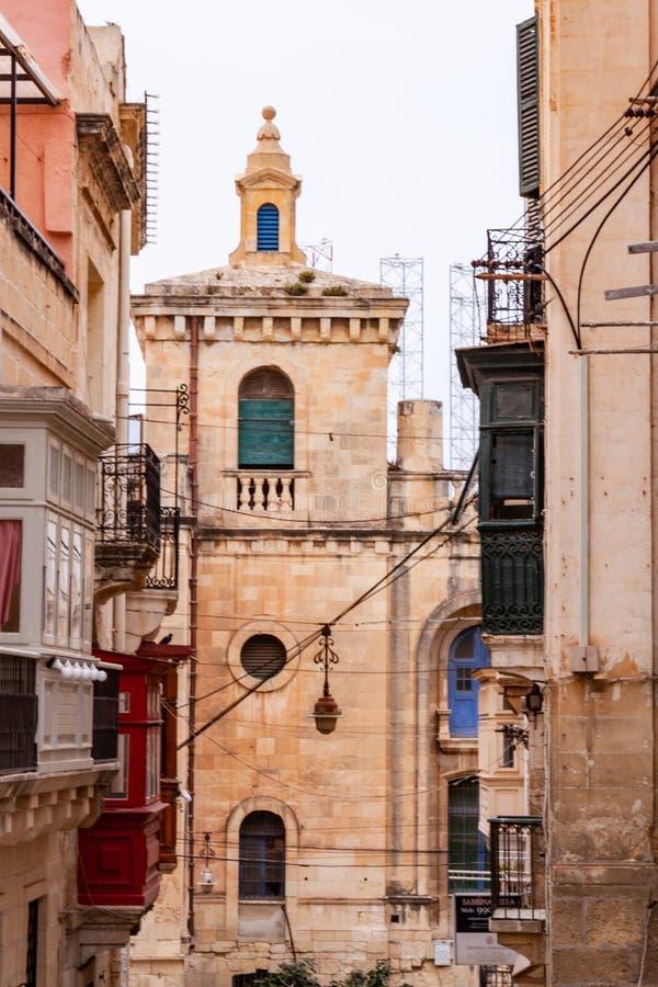 Smala gator och en kyrka av den Valletta staden arkivfoto