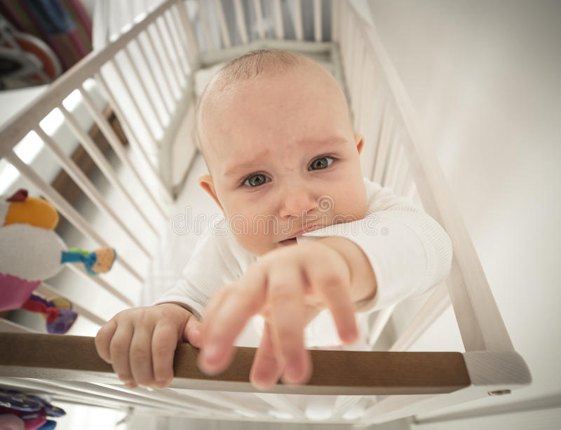 Small abandoned baby in the crib crying. Stretching his hand to wide-angle stock photo