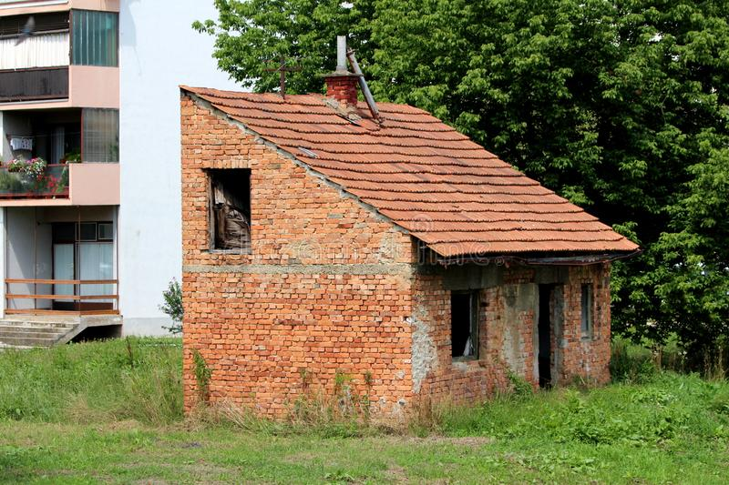 Small abandoned red brick family house with broken missing doors and windows and disconnected electrical wires. Surrounded with uncut grass and tall trees next stock images