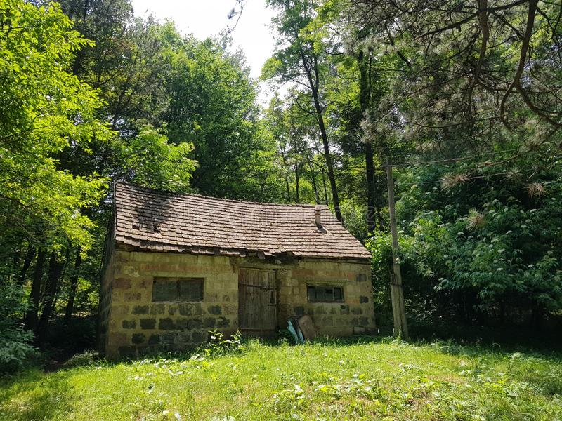 Small abandoned stone house in the middle of a green forest royalty free stock photos