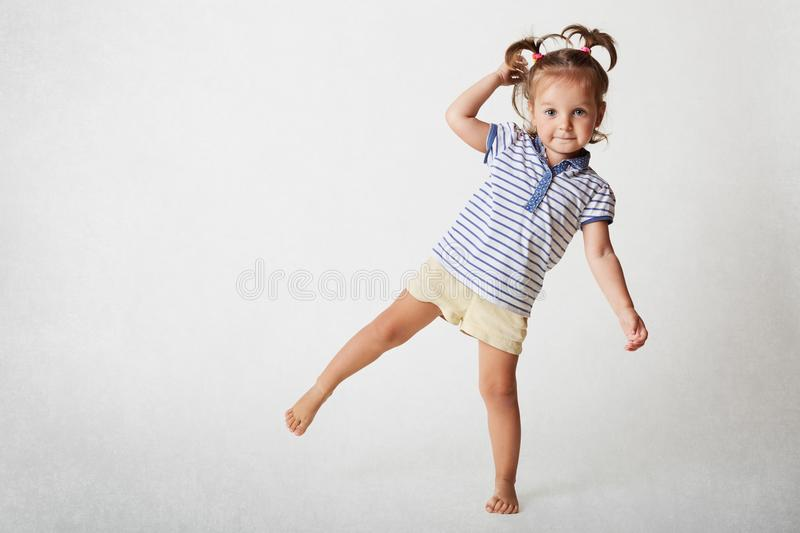 Small adorable female child has funny expression, two pony tails, wears casaul t shirt and shorts, stands on one leg, poses agains royalty free stock photo