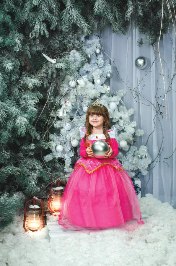Small adorable female child in pink dress holds toy for decoration, decorates New Year tree. Cheerful little kid near stock photo