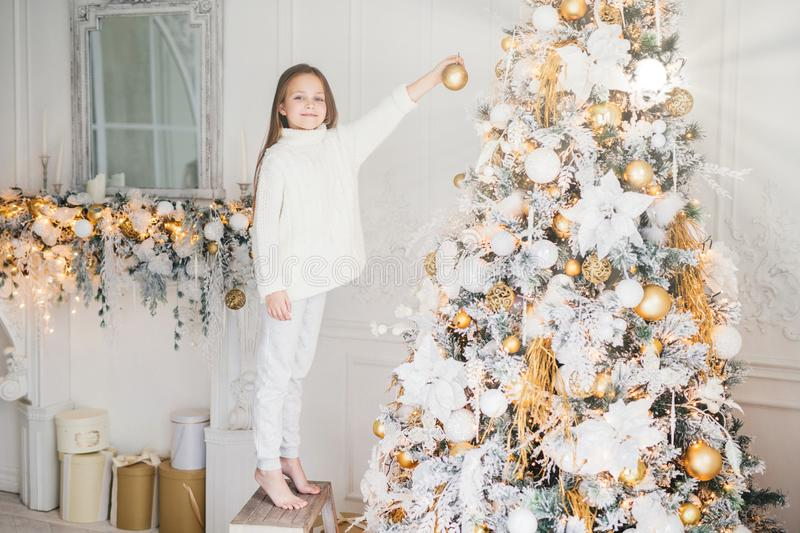 Small adorable female child in white sweater and trousers holds toy for decoration, decorates New Year tree. Cheerful little kid n royalty free stock photography