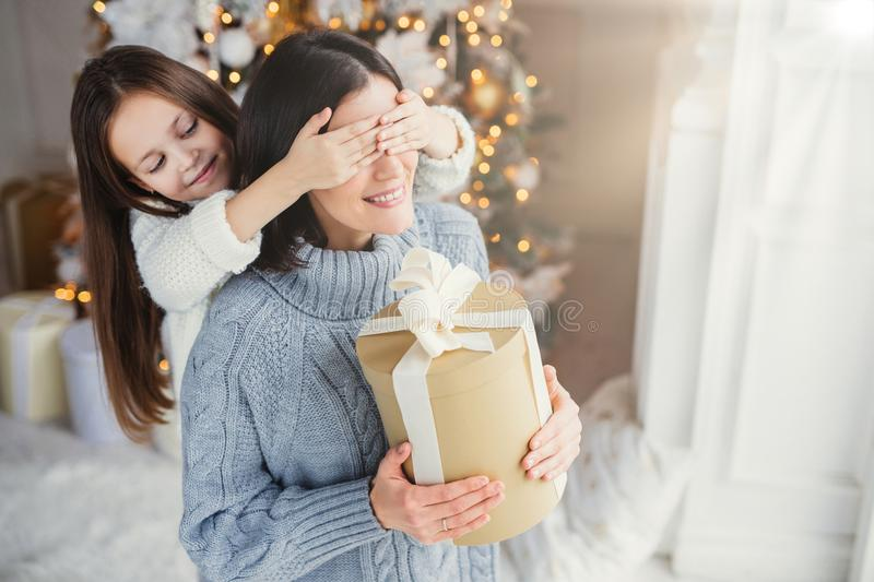 Small adorable female kid prepares surprise for her mother, closes eyes and gives wrapped present as stand at New Year background. stock photos