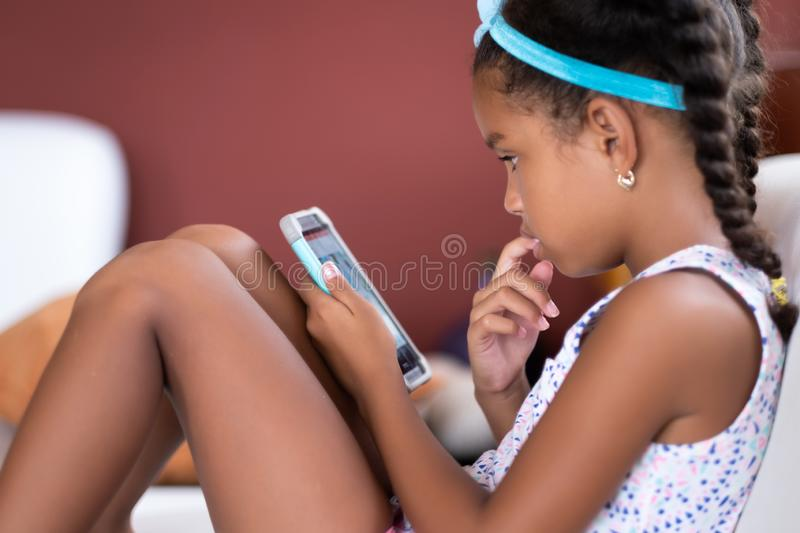 Small african american girl using a mobile phone royalty free stock image
