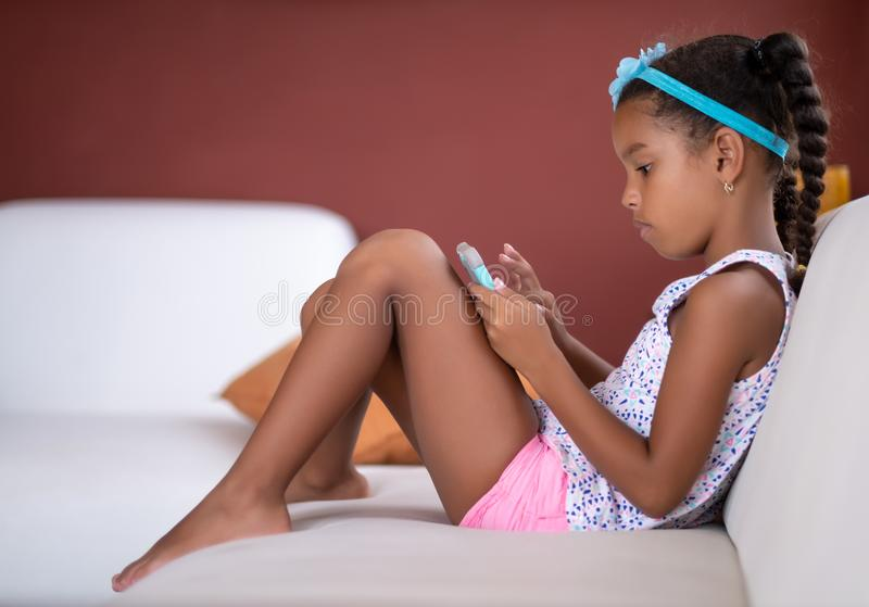 Small african american girl using a mobile phone. At home, african-american, afro, afroamerican, beautiful, biracial, black, browse, cell, cellphone, child royalty free stock photography