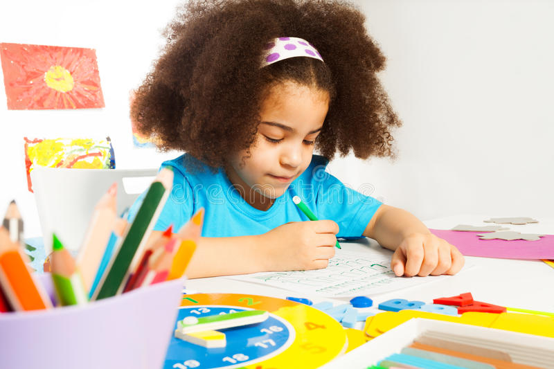 Small African girl writing letters on the paper royalty free stock photography