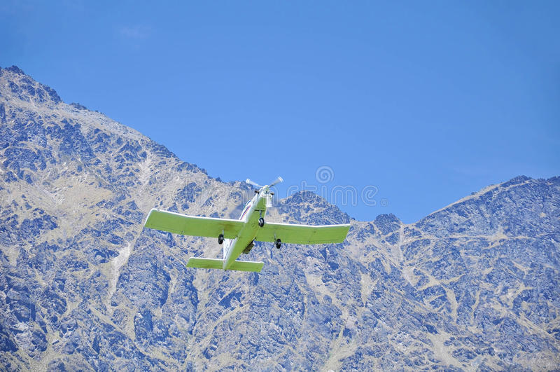 Small aircraft flying low over a field stock photo