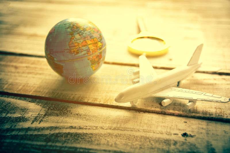 Small airplane and Globe and Magnify Glasses on wooden table tex. Ture background. World map travel and Vacation around the world concept stock image
